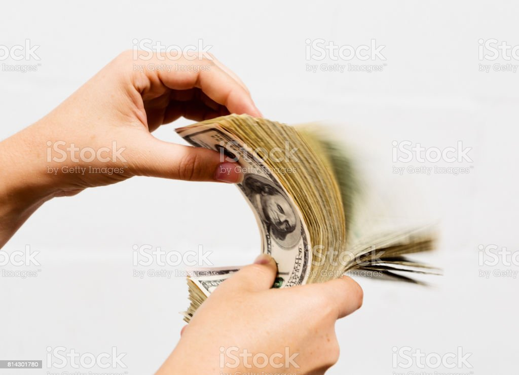 Blurred motion as hand riffles through sheaf of US dollars stock photo
