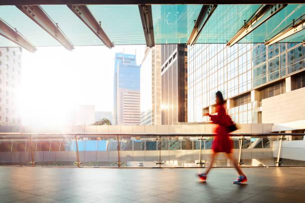 Blurred motion businesswoman walking at pedestrian walkway at dawn stock photo