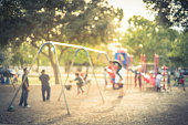 Vintage blurred kids on swing at busy public playground in USA. Defocused children, parents doing activity together. Hanging seat suspended from bar back, forth. Colorful playground in background