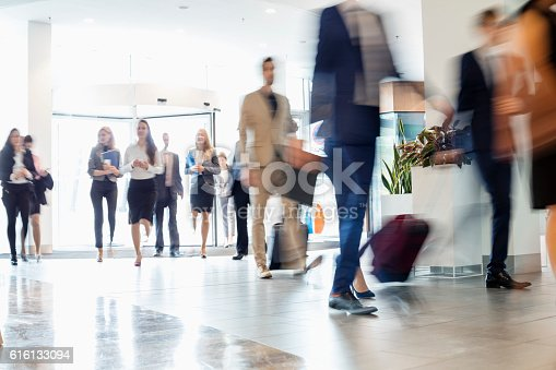 istock Blurred motion of business people walking at convention center 616133094