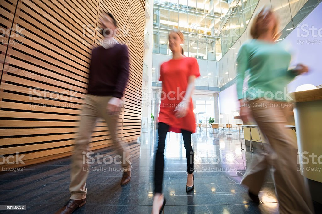 Blurred motion of business people walking in office lobby royalty-free stock photo