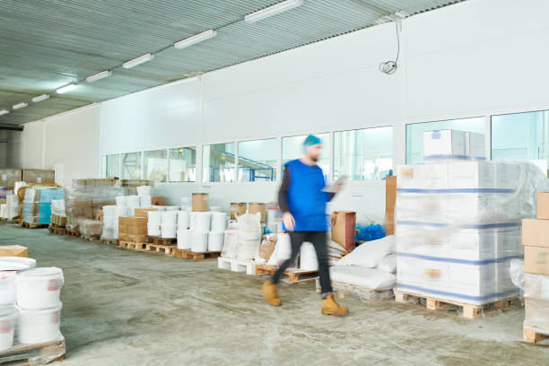 Blurred motion of busy warehouse manager in uniform reading online records on tablet while hurrying to shipment station Factory warehouse of packages food warehouse stock pictures, royalty-free photos & images