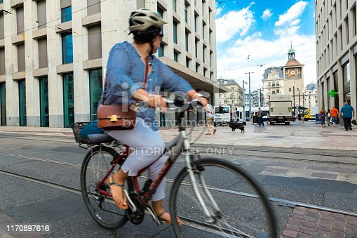Geneva, Switzerland - 6 August, 2019: color image depicting a female cyclist riding her bike on the street in the Swiss city of Geneva. The motion of the cyclist is slightly blurred due to the long exposure used. Room for copy space.