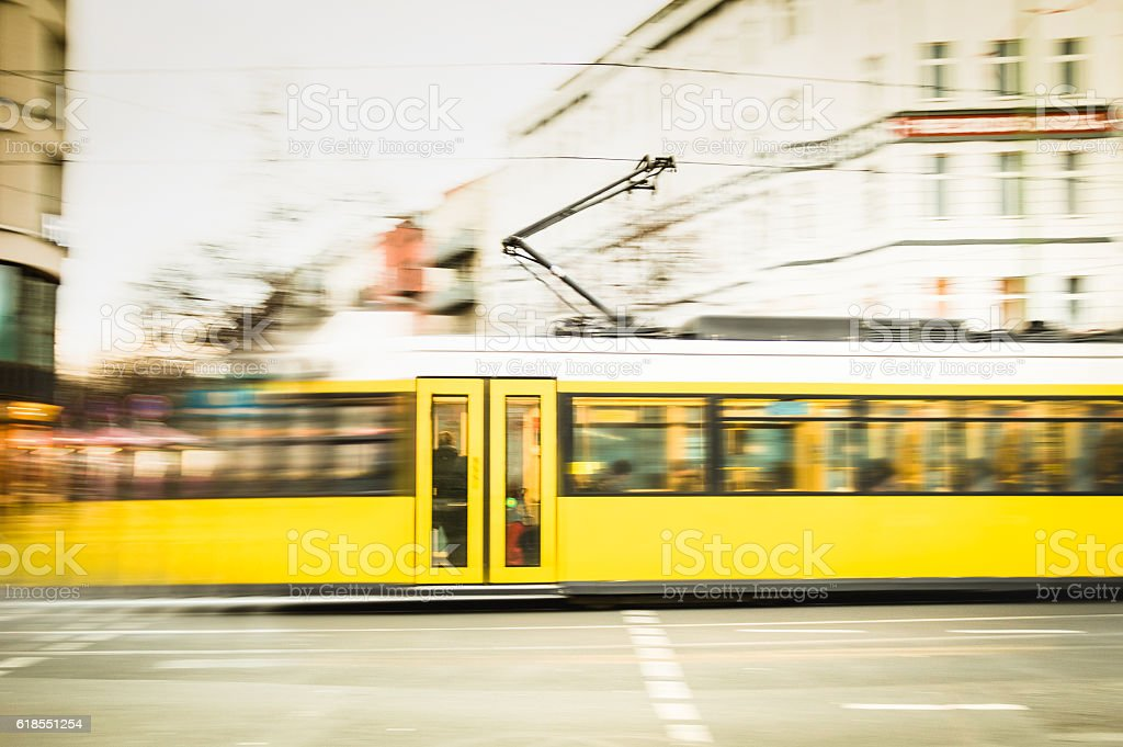 Blurred motion of defocused yellow tram on Berlin streets stock photo