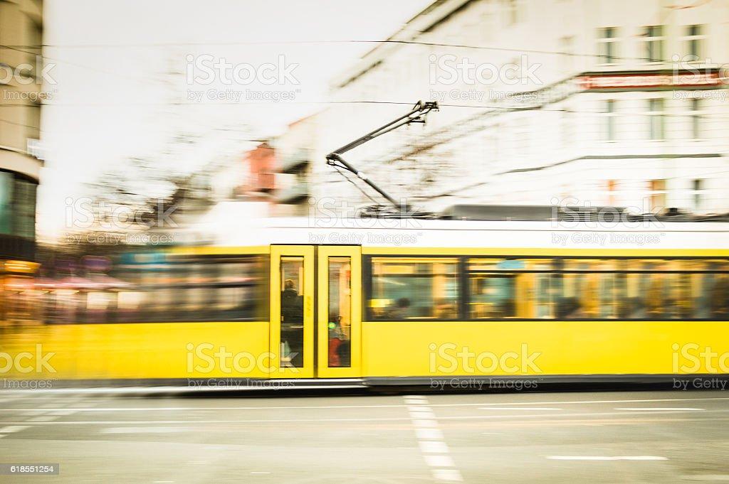 Blurred motion of defocused yellow tram on Berlin streets stock photo