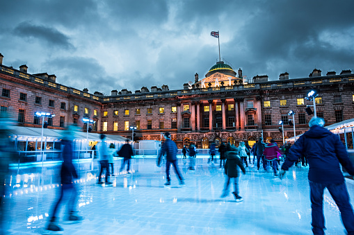 Blurred motion of crowds of people ice skating at Somerset House, a publically owned building in central London. The image features warm evening light, and an ominous, moody sky. The people appear as unrecognisable blurs due to the long exposure used. Somerset House is a large Neoclassical building situated on the south side of the Strand in central London, overlooking the River Thames, just east of Waterloo Bridge.