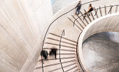Color image depicting an abstract high angle view of a concrete spiral staircase. We can see the blurred motion of a group of people walking up and down the staircase, giving the impression that they are moving fast.  Room for copy space. ***image taken in City Hall, London, UK, a publicly owned building freely accessible to the public without entry fees or photographic restrictions***