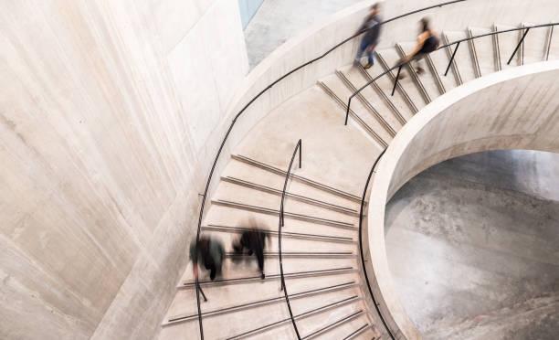 verschwommene bewegung von menschen auf spiraltreppe - treppe stock-fotos und bilder