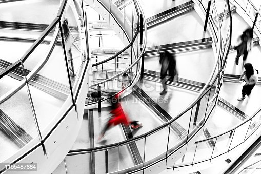 180698194 istock photo Blurred Motion of People Running down Futuristic Modern Spiral Staircase 1155487684