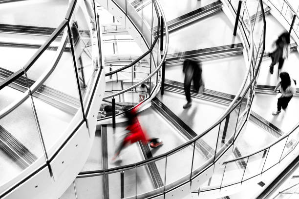 Blurred Motion of People Running down Futuristic Modern Spiral Staircase High angle image depicting an abstract view of a group of people running down a modern spiral staircase in the city. The running is depicted as motion blur, which makes it looks as though the people are moving extremely fast. Everything in the image is desaturated except one female who is dressed entirely in red. Room for copy space. ***IMAGE SHOT IN CITY HALL, LONDON, UK, A PUBLICLY OWNED BUILDING FREELY ACCESSIBLE TO THE PUBLIC. PLEASE NOTE THERE NO FEES OR TICKETS ARE REQUIRED TO ENTER, AND THERE ARE NO PHOTOGRAPHIC RESTRICTIONS*** desaturated stock pictures, royalty-free photos & images