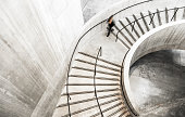 Wide angle color image depicting an abstract high angle view of a concrete spiral staircase. We can see the blurred motion of a person climbing up the spiral staircase, giving the impression that he or she is moving fast.  Room for copy space. ***image taken in City Hall, London, UK, a publicly owned building freely accessible to the public without entry fees or photographic restrictions***