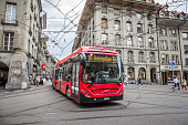 Bern, Switzerland - 6 August, 2019: Color image depicting the blurred motion of a red public passenger bus on the streets of central Bern, the capital city of Switzerland. Room for copy space.