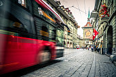 Color image depicting the blurred motion of a red public passenger bus on the streets of central Bern, the capital city of Switzerland. Room for copy space.