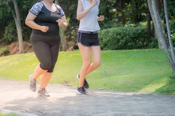 太った女性と薄い女性の動き、ぼやけて運動公園でジョギングをして、健康のため実行しているし、重量を失います。 ストックフォト