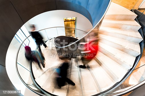180698194 istock photo Blurred Motion of Urban People Running down Futuristic Modern Spiral Staircase 1213000674