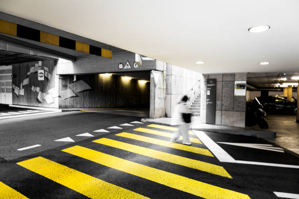 Blurred motion of urban person walking across yellow striped pedestrian crossing Wide angle color image depicting the blurred motion of a person walking across a vibrant yellow-colored pedestrian crossing in an urban underground car park. The person is unrecognisable. The leading lines of the crossing and other road markings, along with the modern urban architecture, make for a dramatic composition. desaturated stock pictures, royalty-free photos & images
