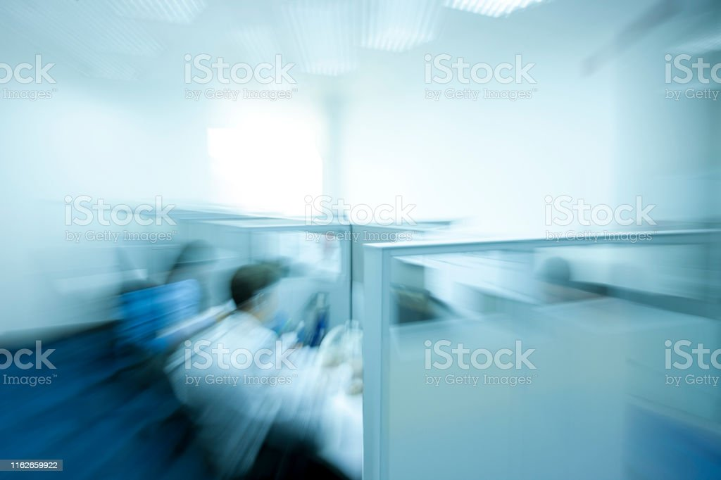 Workers in office cubicles, defocused. Blurred motion. Business....