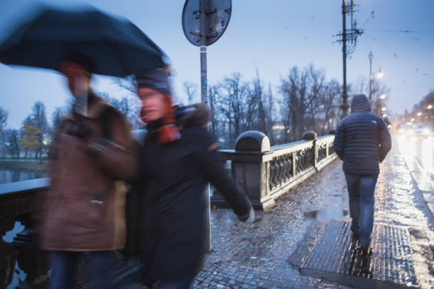 blurred motion people going over the bridge in the rain in Prague stock photo