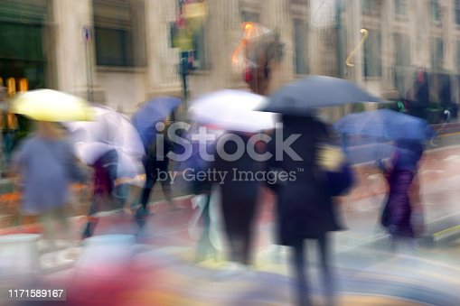 blurred motion people walking in rain day on busy street of Manhattan in New York, USA