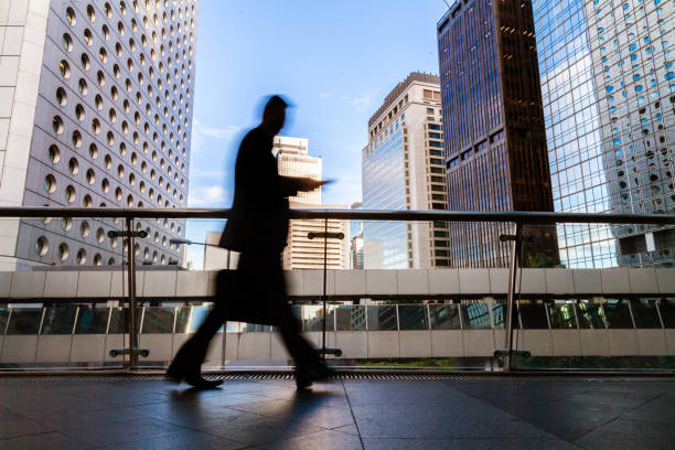 Blurred motion silhouette of businessman walking in Hong Kong's Central District elevated walkway stock photo