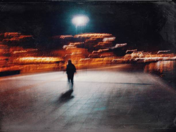 Blurred motion view of the man walking in the street at night