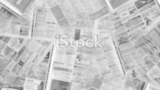 Old ripped newspapers on horizontal surface. Blurred background texture
