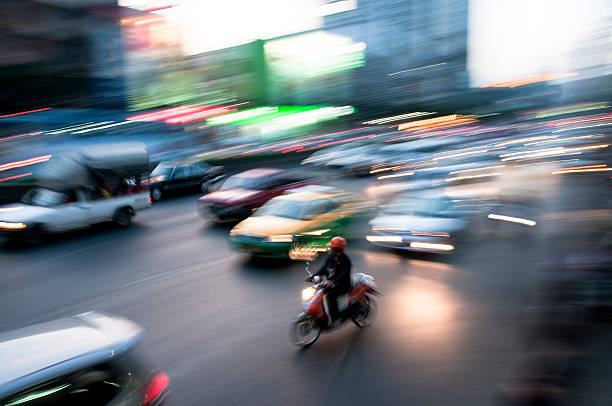 blurred night traffic in bangkok, thailand - motorbike, umbrella stock pictures, royalty-free photos & images