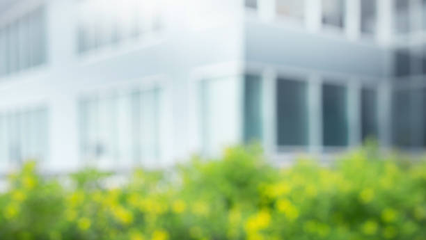 Blurred of glass wall from architecture building and flower garden.For use key visual design stock photo