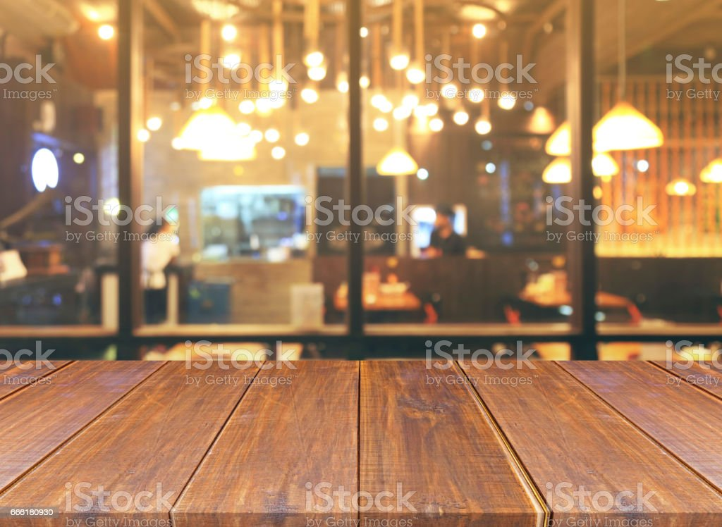 Blurred of restaurant with bokeh lights background and wood table stock photo