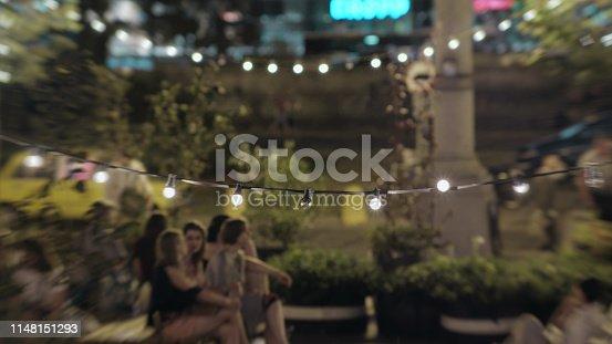 Night garden party, illuminated trees. Blurred motion