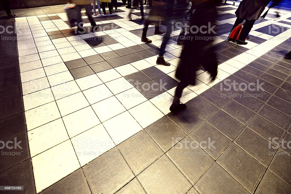 Blurred pedestrians on tiled square royalty-free stock photo