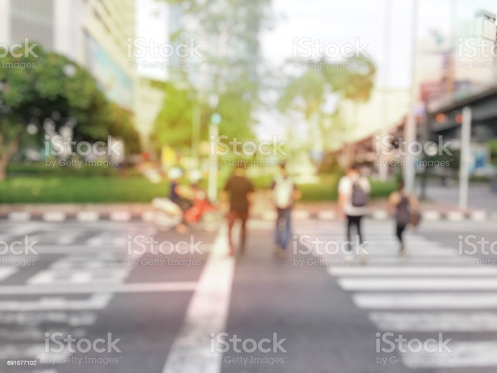blurred image of people crowd on zebra crossing and are moving across...