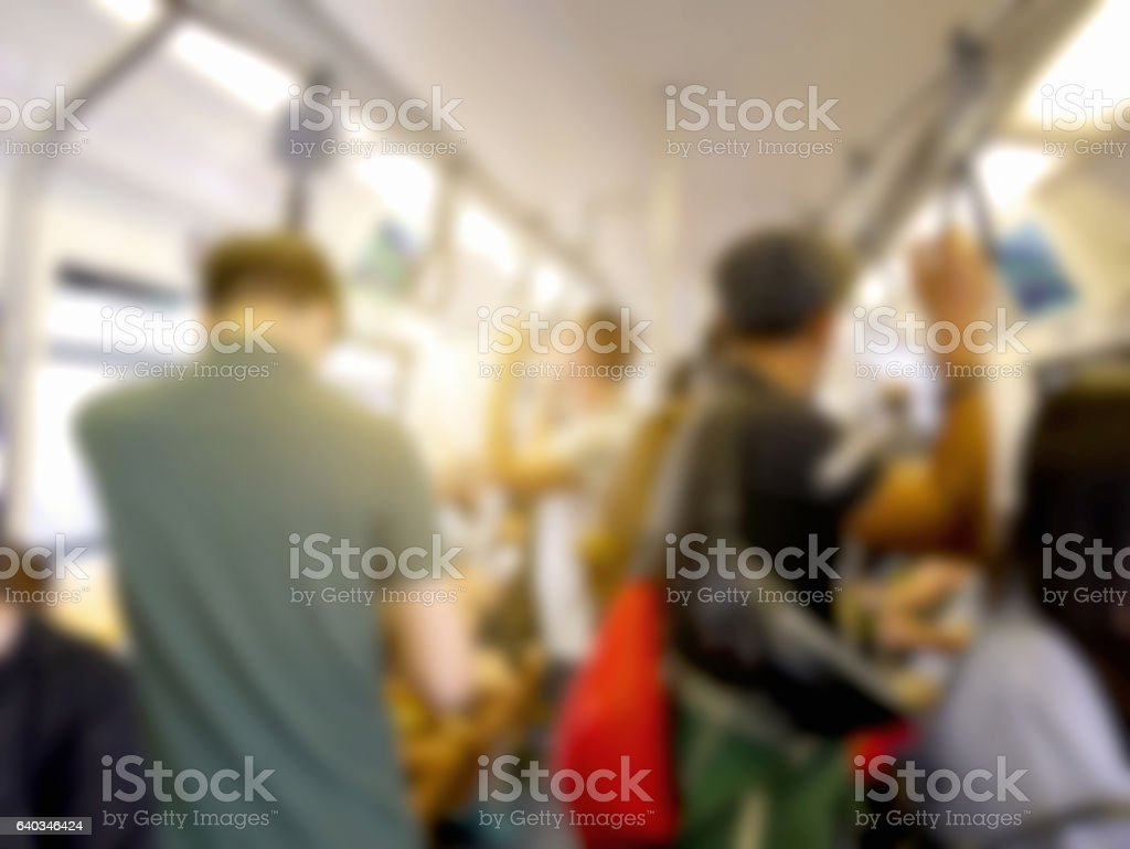 Blurred people hold strap while standing on the train stock photo