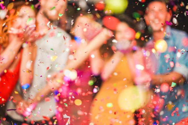 partido haciendo borrosa de la gente tirando confeti - jóvenes celebrando el fin de semana noche - entretenimiento, diversión, fin de año, vida nocturna y fiesta concepto - desenfocada foto - fiesta fotografías e imágenes de stock