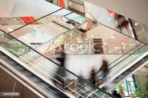 istock Blurred People on Escalator in Modern Glass Interior 154003330