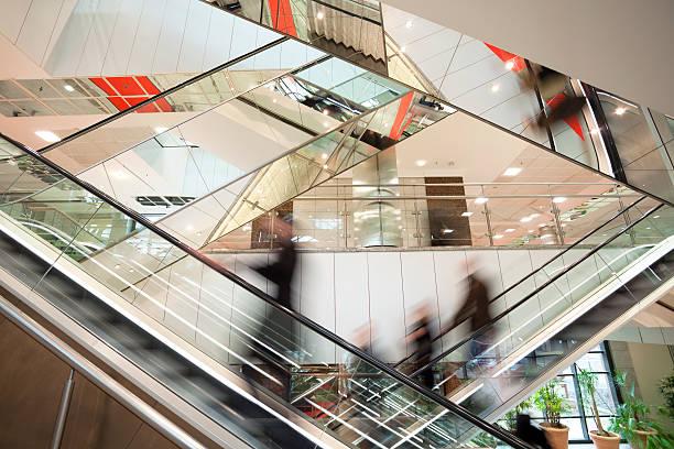 offuscata persone su scale mobili in interni moderni di vetro - escalator foto e immagini stock