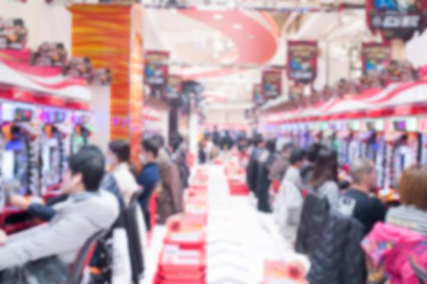 verschwommene menschen spielen pachinko spielautomaten in tokio - pinball spielen stock-fotos und bilder