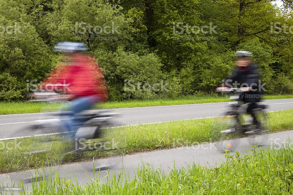 Blurred People Riding Bicycles Along a Country Road royalty-free stock photo