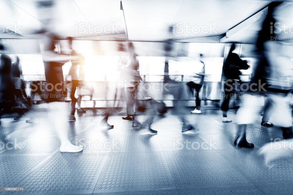 Blurred people walking in a corridor stock photo