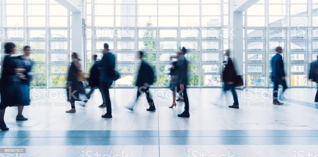 Businesspeople walking in a modern hall.