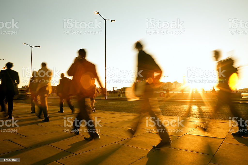 Blurred people walking in sunset light stock photo