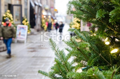 Blurred people walking of Petit Champlain street with Christmas tree in foreground downtown Quebec city during day of autumn