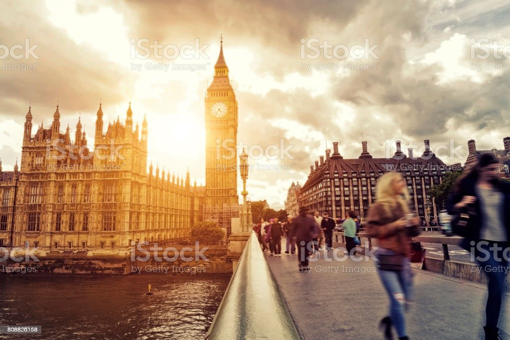 Blurred people walking on Westminster Bridge at sunset stock photo