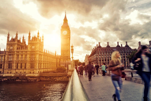 Blurred people walking on Westminster Bridge at sunset Dramatic sky over the Houses of Parliament at sunset city of westminster london stock pictures, royalty-free photos & images