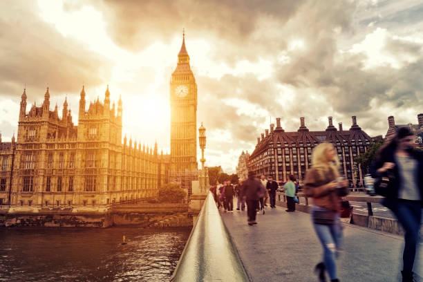 borrosa la gente caminando sobre el puente de westminster al atardecer - memorial day fotografías e imágenes de stock