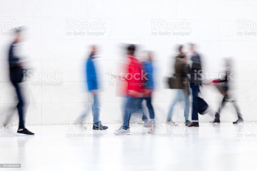 Verschwommene Menschen zu Fuß auf weißen Flur – Foto