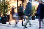 Blurred People Walking Past Illuminated Fashion Store