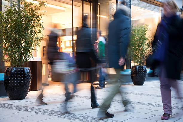 verschwommene leute gehen vergangenheit beleuchtet mode-store - arbeit in münchen stock-fotos und bilder