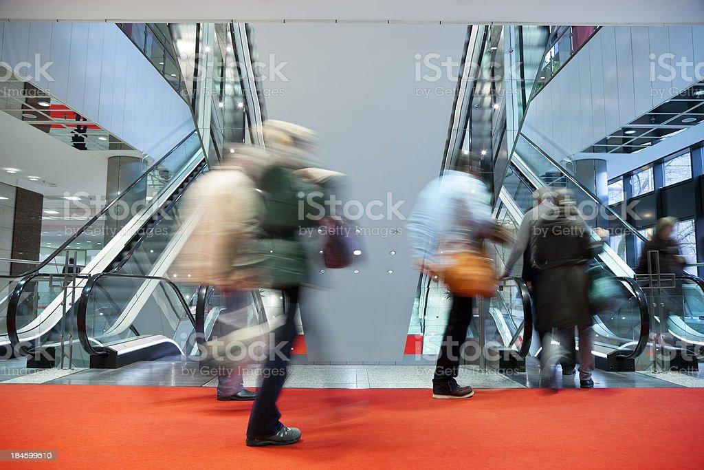 Blurred People Walking Red Carpet to Escalator in Modern Interior stock photo
