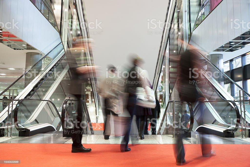 Blurred People Walking Red Carpet Towards Escalators in Modern Interior stock photo